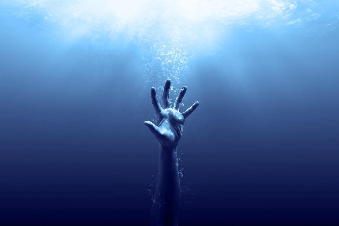 Hand reicht unter Wasser nach oben und will die Wasseroberfläche erreichen