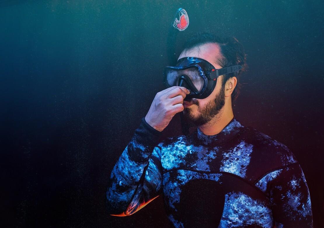 Taucher hält sich unter Wasser die Nase zu und taucht ab