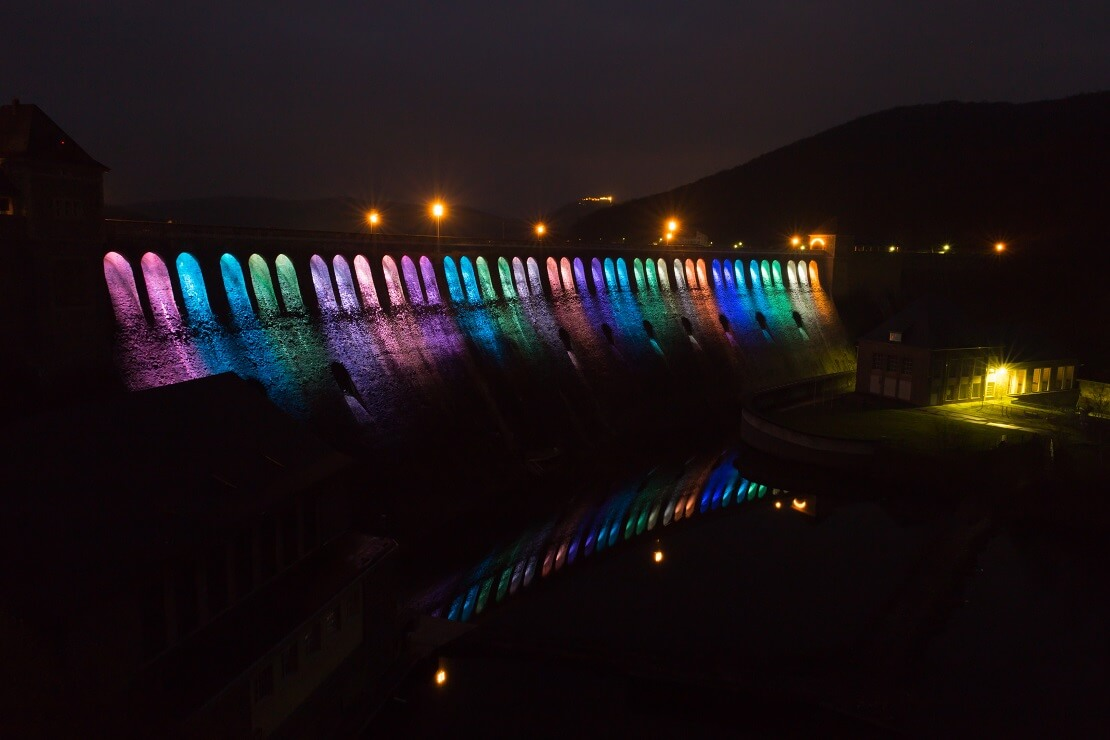 Speermauer am Edersee leuchtet in bunten Farben bei Dunkelheit