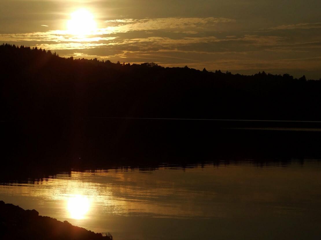 Ein See umgeben von Mergen im Hintergrund geht die Sonne unter