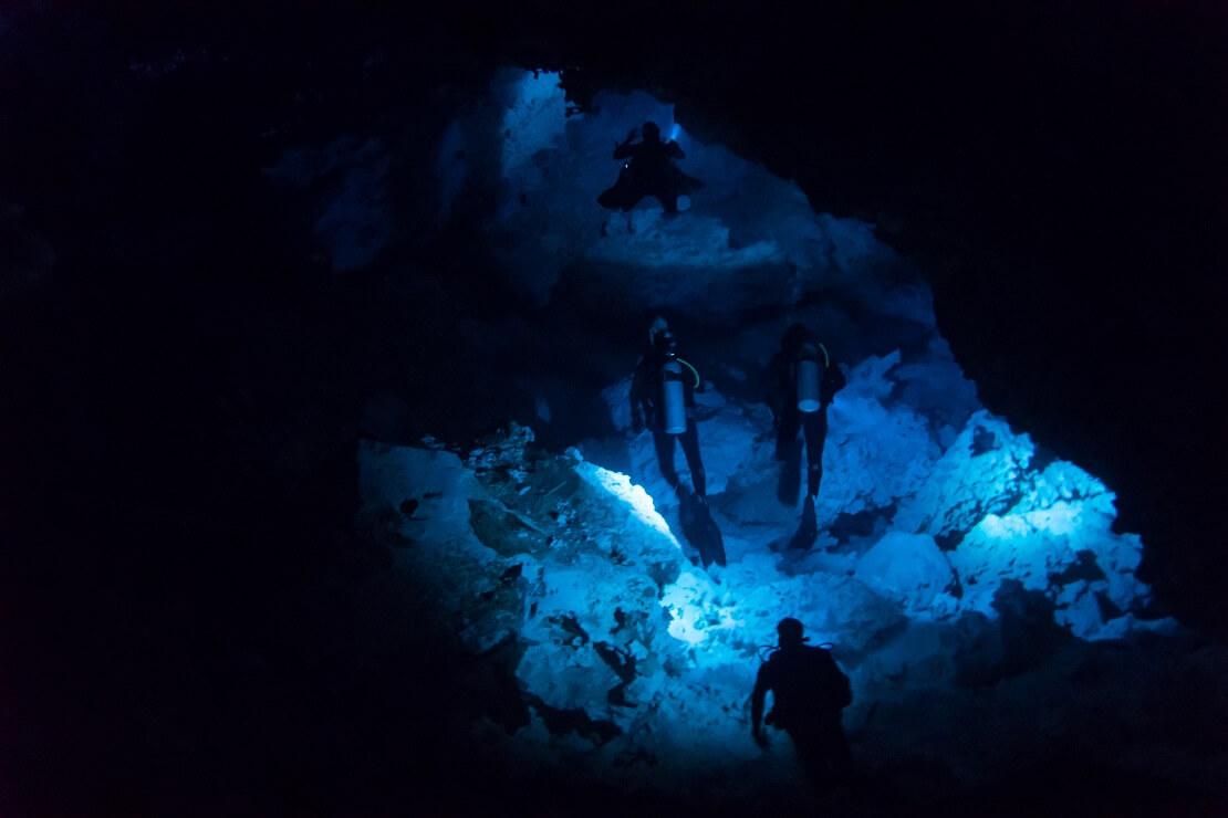 Drei Taucher tauchenin einer Dunkeln Höhle durch einen Tunnel