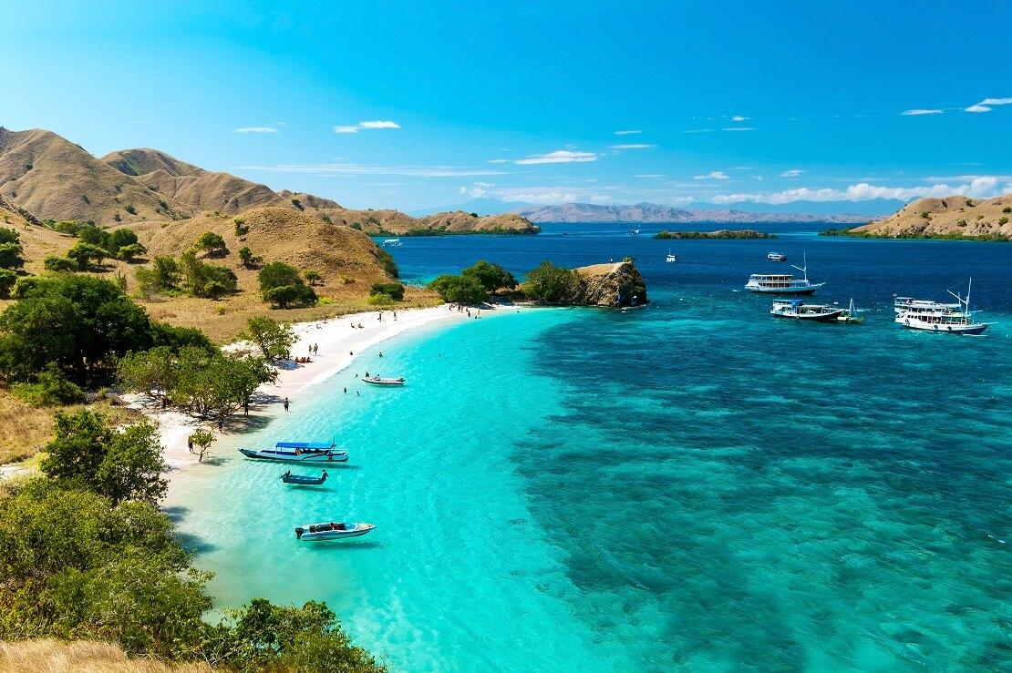 An der Küste von Komodo ist weißer Sand un türkis blaues Wasser und blauer Himmel