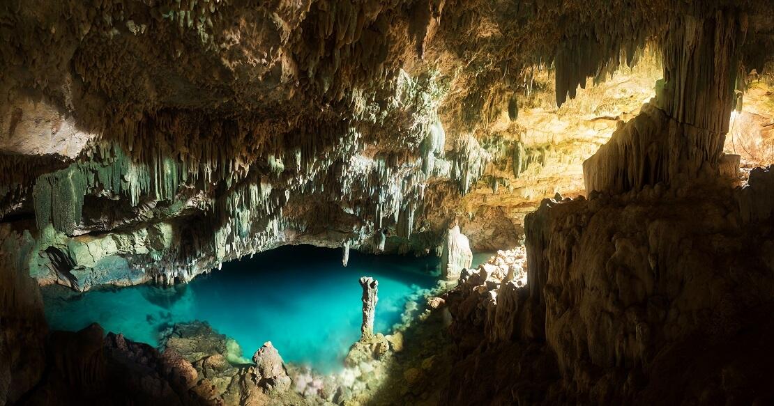 Eine Höhle mit türkis blauem Wasser von der Decke hängen Stagnierten