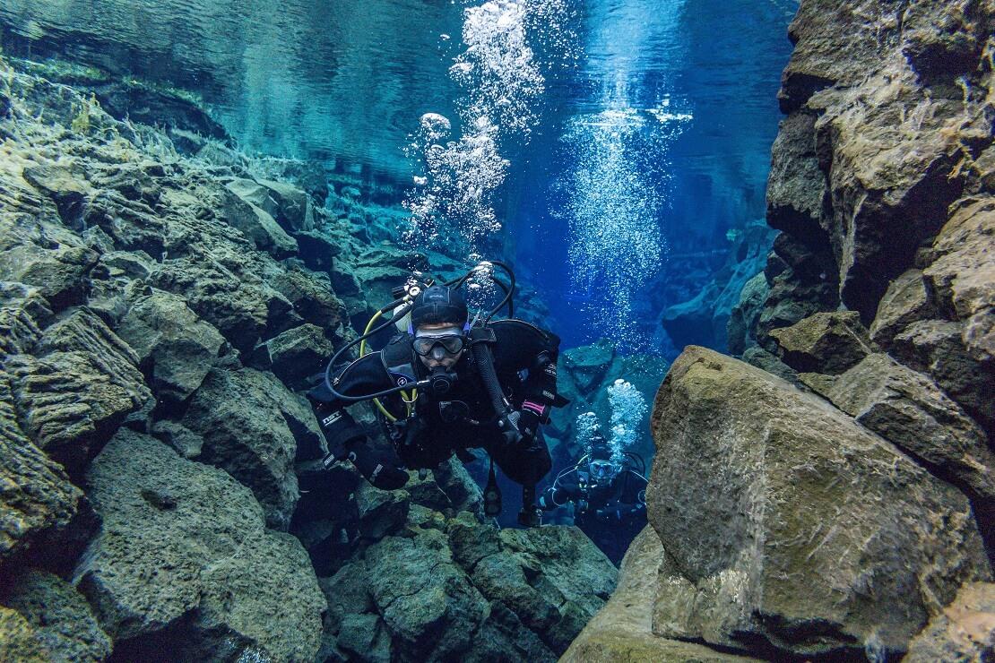 Taucher schwimmt zwischen Felsen im klaren Wasser