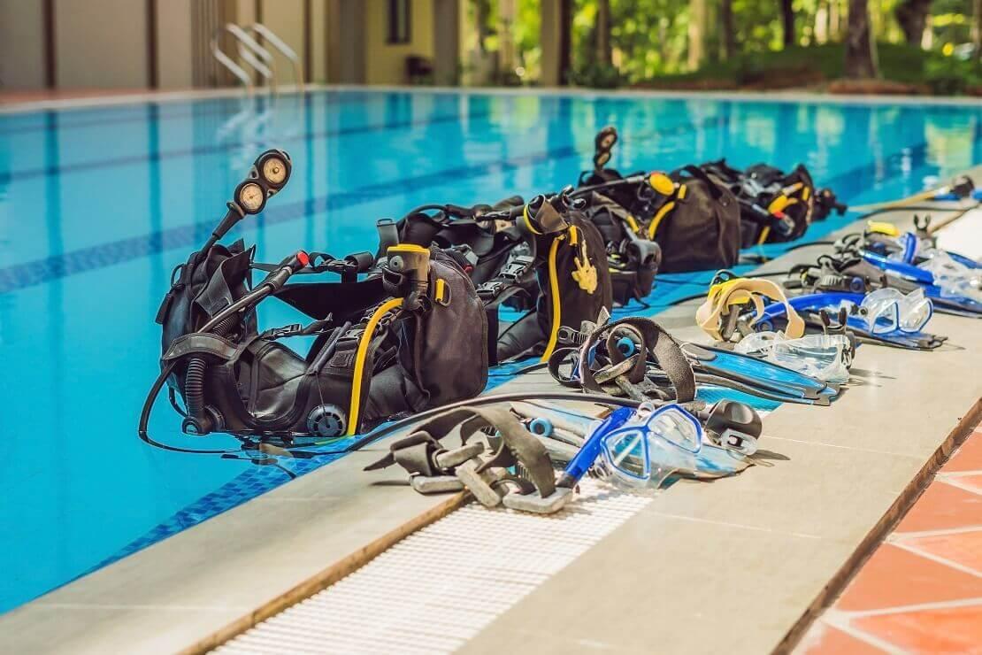 Viele Tauchausrüstungen liegen nebeneinander am Beckenrand eines Schwimmbeckens.