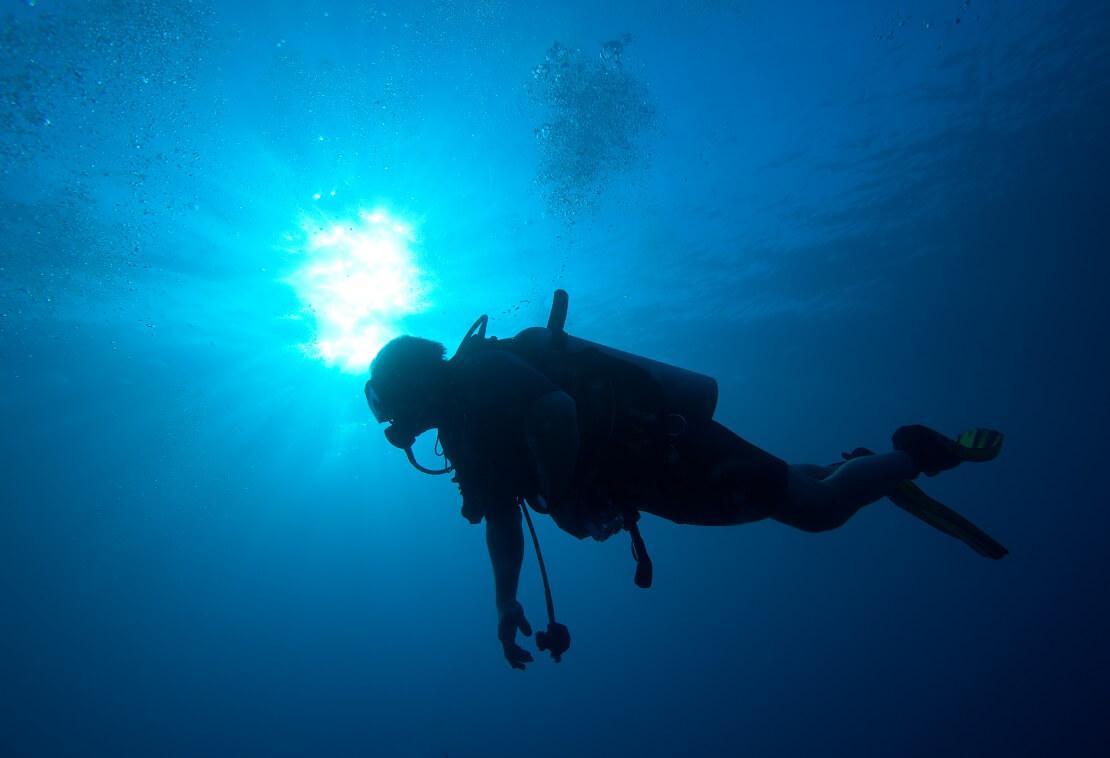 Taucher mit Ausrüstung unter der Wasseroberfläche