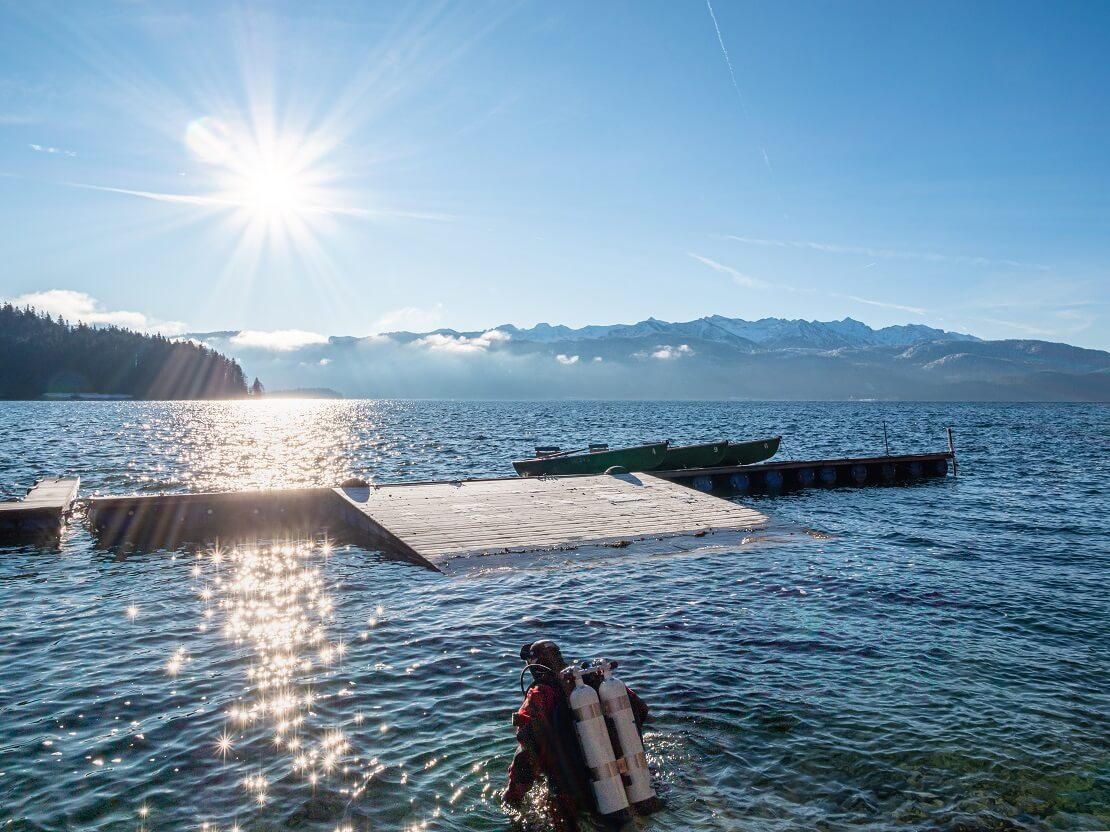 Taucher steigt mit Ausrüstung bei Sonnenschein in den See ein