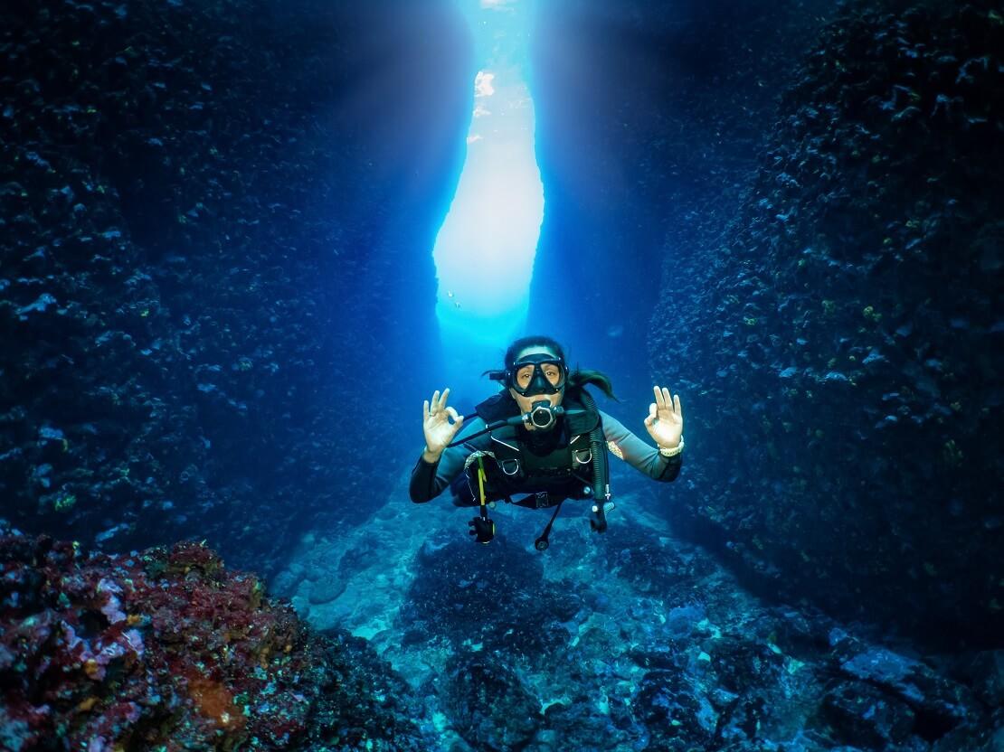 Taucherin vor einer Höhle unter Wasser zeigt das alles OK ist