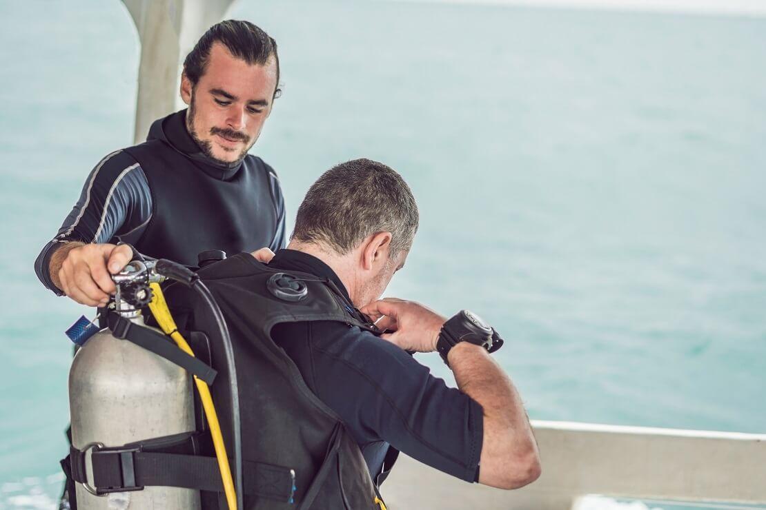 Taucher hilft seinem Partner auf einem Boot die Tauchausrüstung anzuziehen