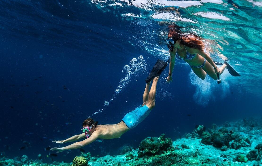 Zwei Taucher Schnorcheln im türkis blauen Meer