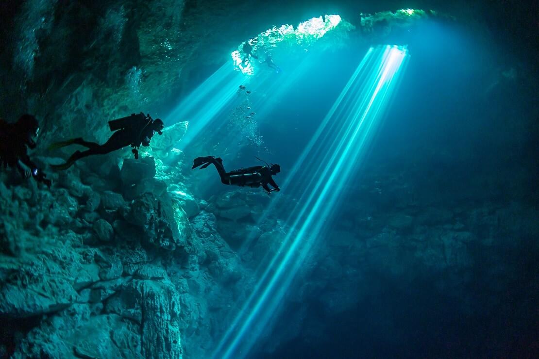Taucher in einer Höhle unter Wasser im türkis blauen Meer