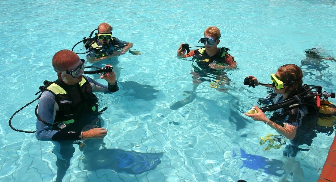 Taucherlehrer erklärt seinen Schülern im Pool die Tauchaustüstung