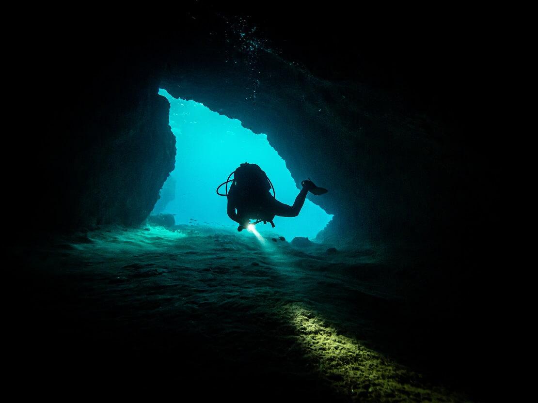 Taucher schwimmt durch schmalen Tunnel unter Wasser