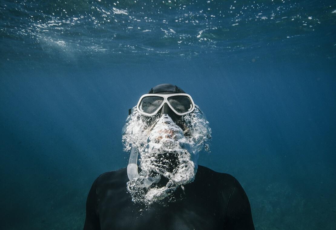 Apnoetaucher taucht an die Wasseroberfläche auf und lässt Blasen