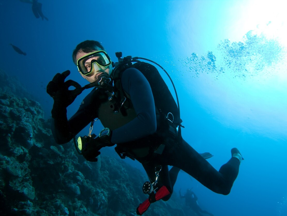 Taucher mit Ausrüstung unter Wasser und zweigt das alles OK ist