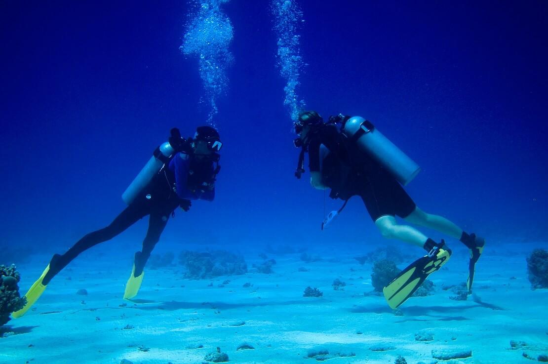 Zwei Taucher am Meeresgrund im blauen Meer gucken sich gegenseitig an