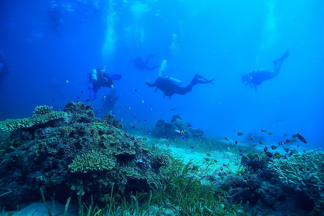 Taucher atmen unter Wasser und werfen dabei Blasen