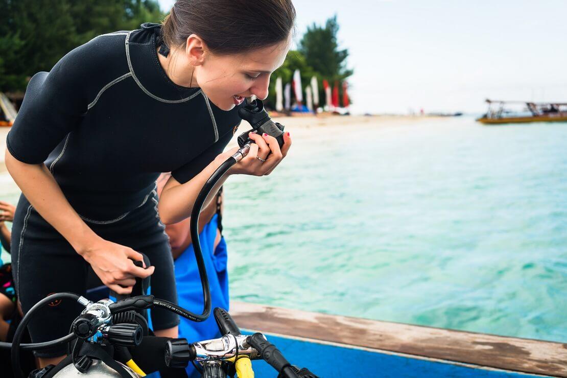 Taucherin prüft Ausrüstung am Meer