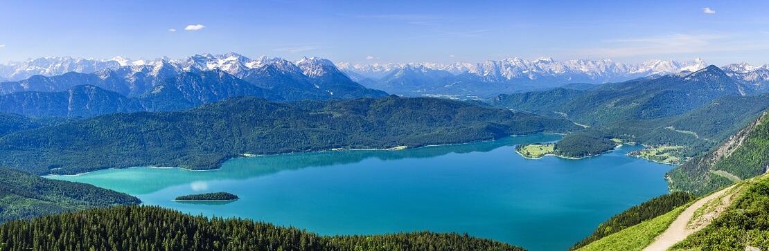 Ansicht des Walchensees türkis blauer See umgeben von den Alpen und einem Wald