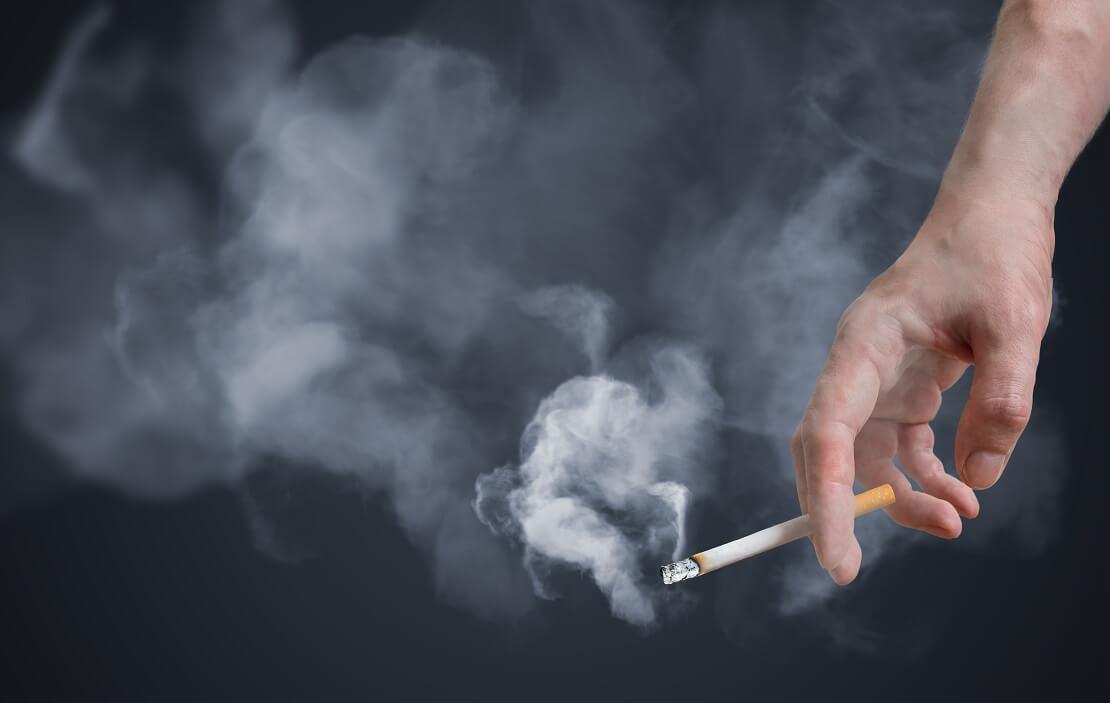 Person hält Zigarette in der Hand welche qualmt