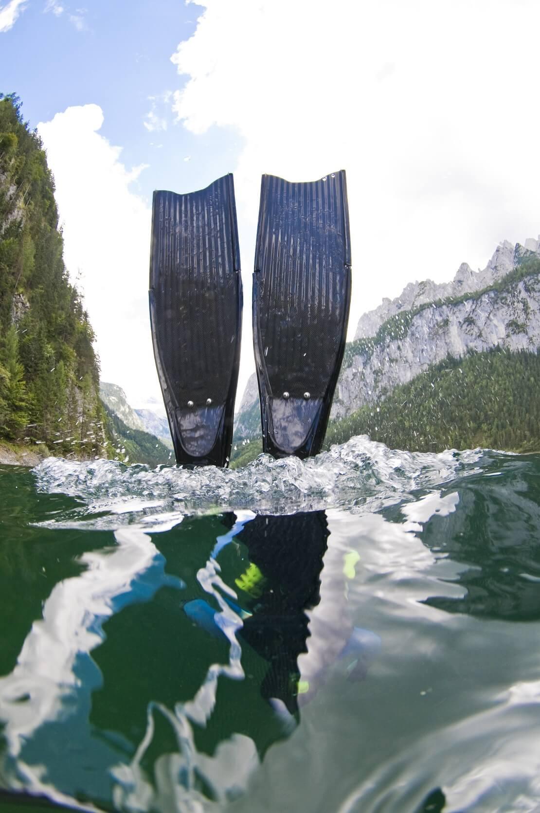 Apnoeflossen im Wasser im Hintergrund sind Berge zu sehen