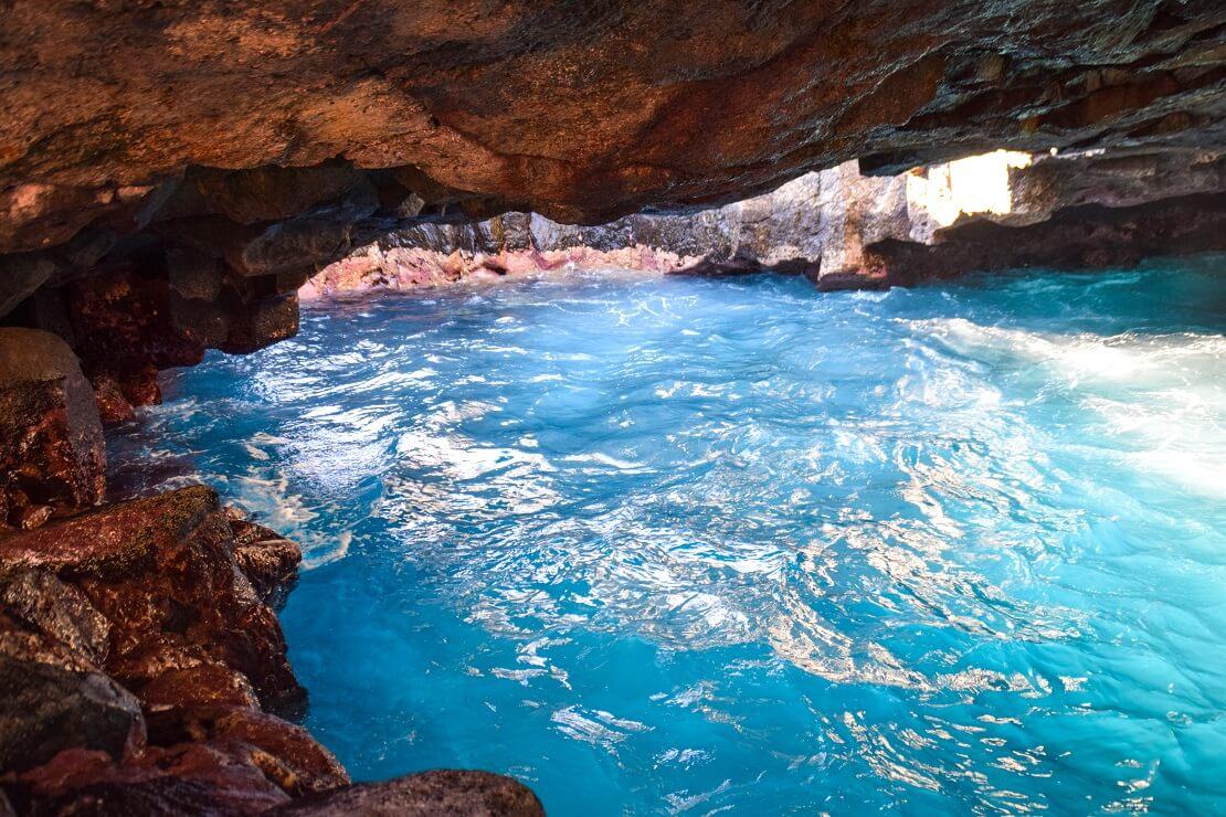 Felsige Höhle mit klarem und blauen Wasser