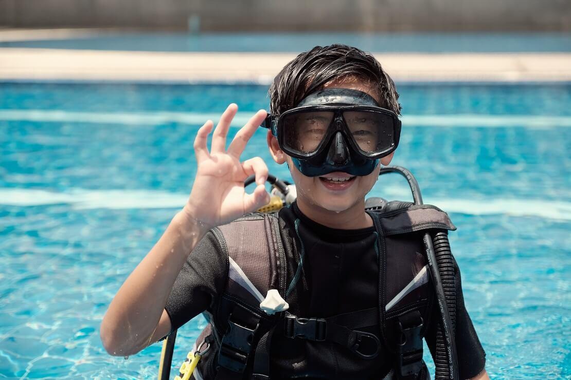 Junge steht mit Tauchausrüstung im Wasser