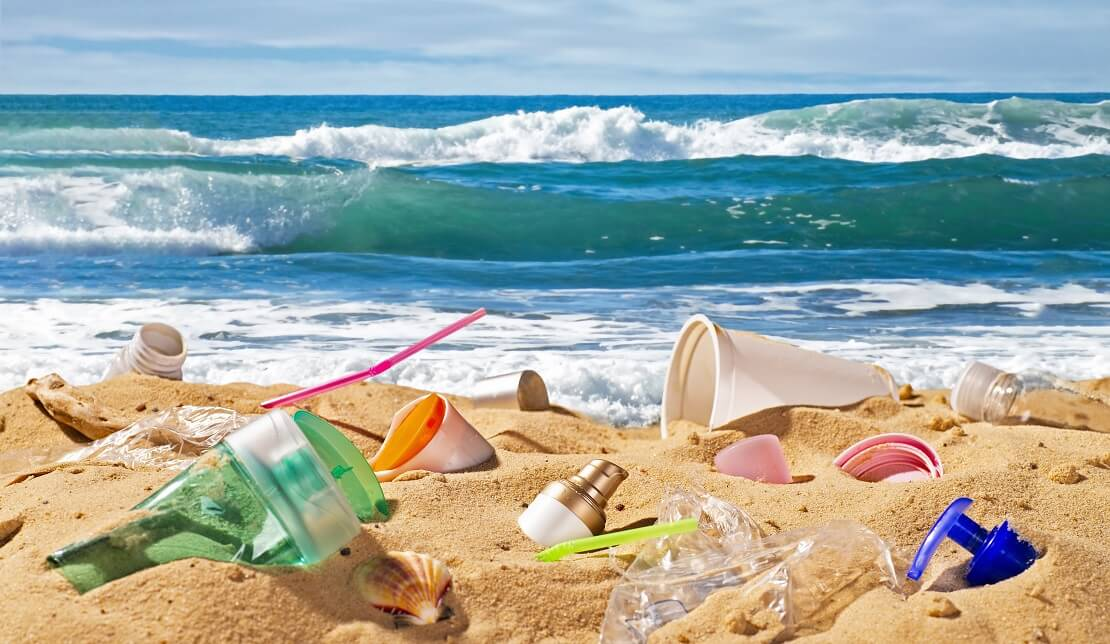 Müll liegt auf einem Sandstrand im Hintergrund ist das Meer