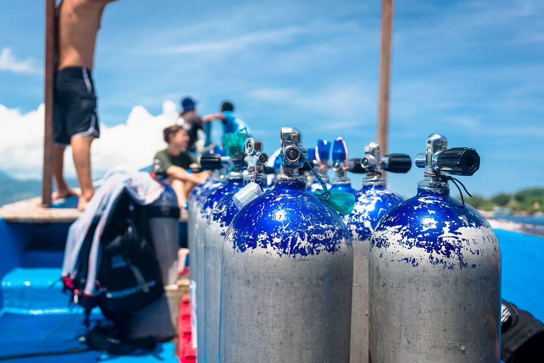 Taucher sind mit Pressluftflaschen auf einem Boot im Wasser