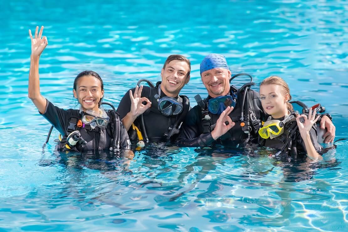 Vier Personen stehen zur hälfte im Wasser mit Tauchausrüstung und zeigen das alles ok ist