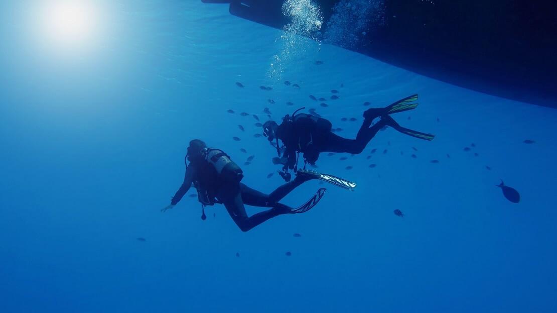 Taucher tauchen unter einem Boot um sie schwimmen Fische