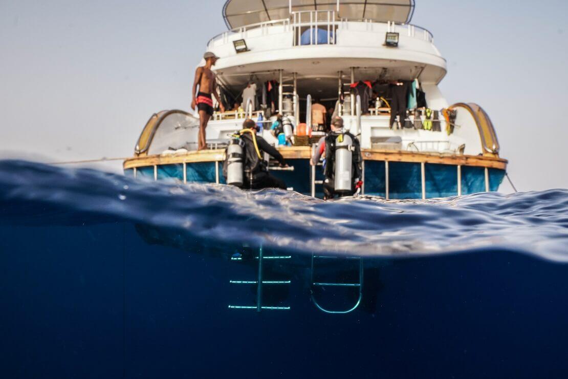Taucher steigen die Leiter von einem Boot ab und Tauchen in das Wasser ein