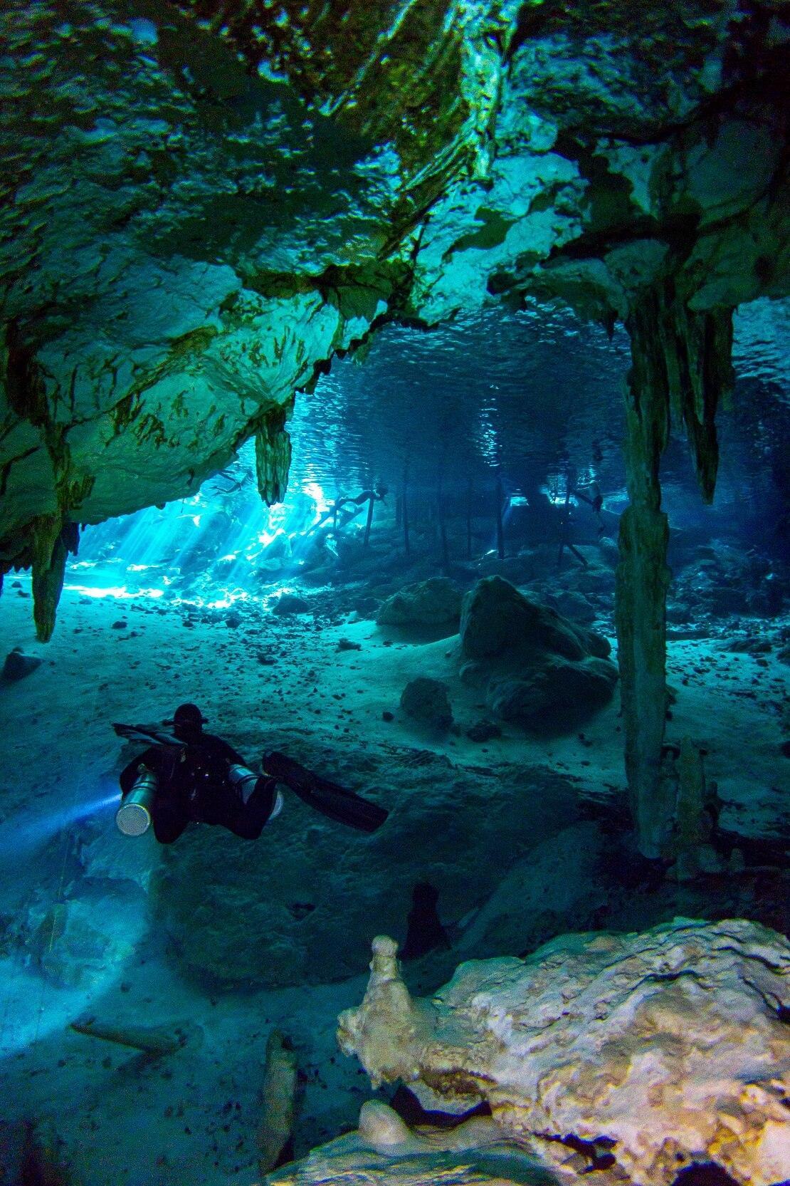 Taucher schwimmt in einer Unterwasserhöhle in glasklarem Wasser