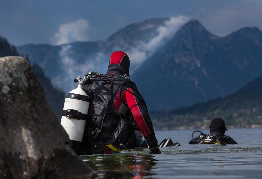 Taucher steigt mit Ausrüstung zwischen den Bergen ins Wasser ein