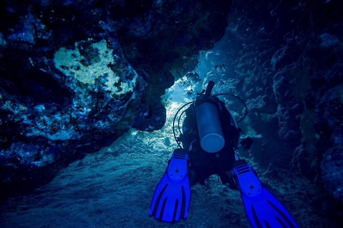 Taucher taucht durch eine schmale Höhle