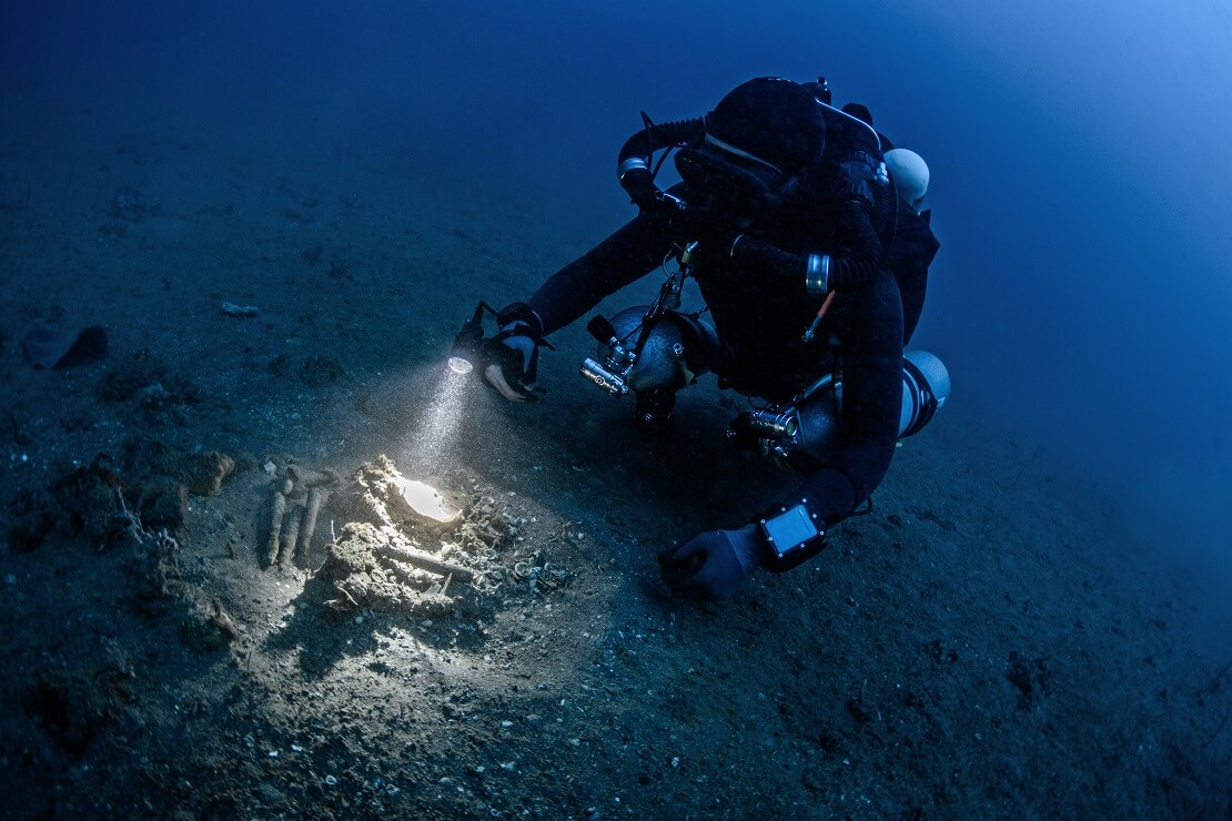 Taucher am Meeresgrund leuchtet mit einer Taschenlampe auf dem Sand