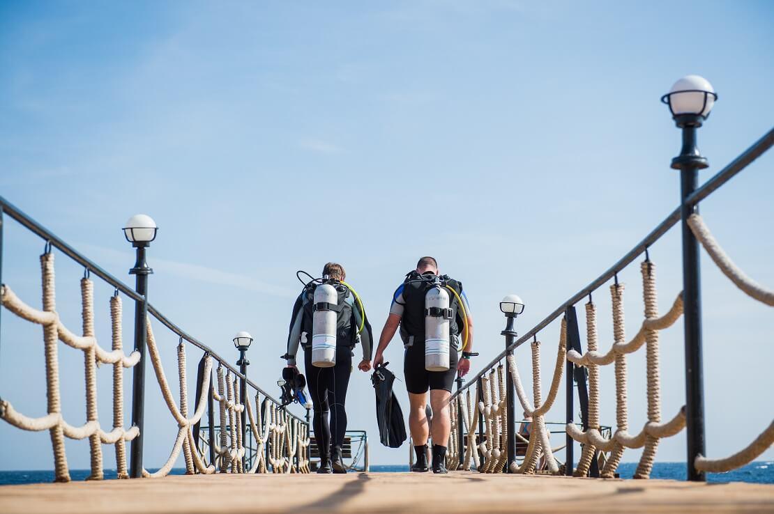 Zwei Taucher laufen auf einem Steg mit Tauchausrüstung