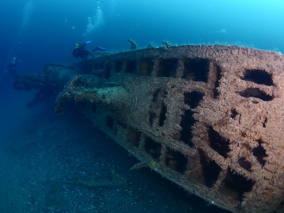 Taucher schwimmen um ein versunkenes U-Boot herum