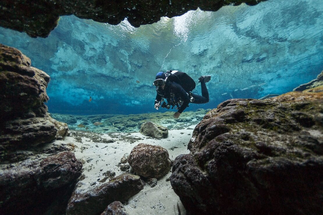 Taucher zwischen Felsen im klaren Wasser