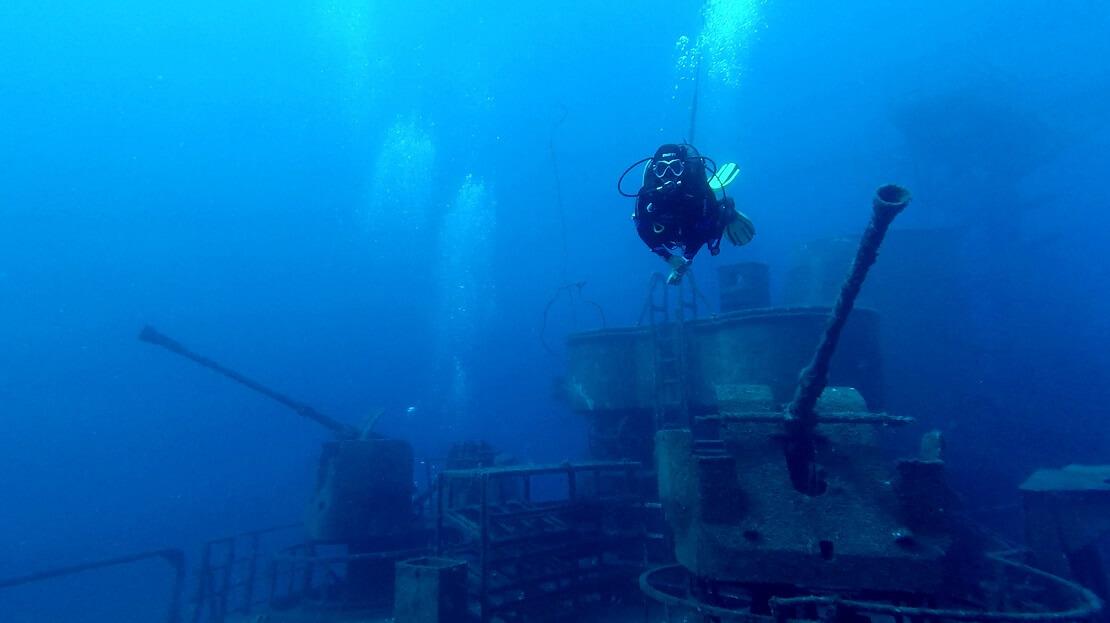 Taucher schwimmt über einem Schiffswrack