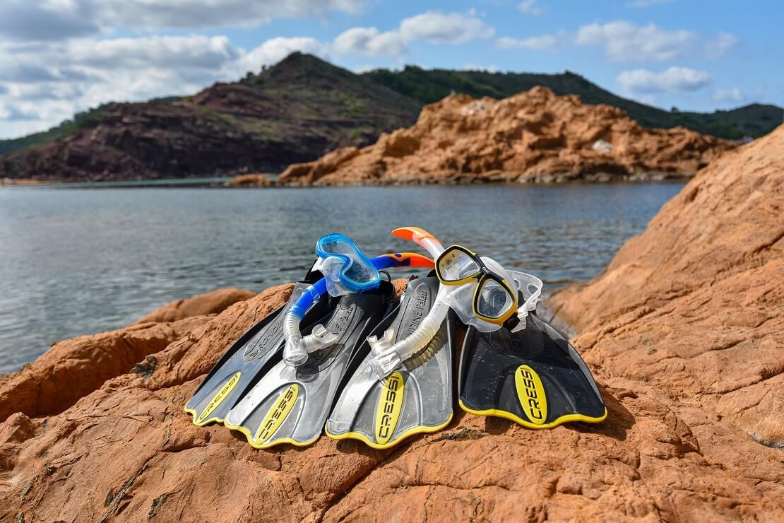 Flossen, Taucherbrille und Schnorchel liegen auf einem Felsen neben dem Wasser