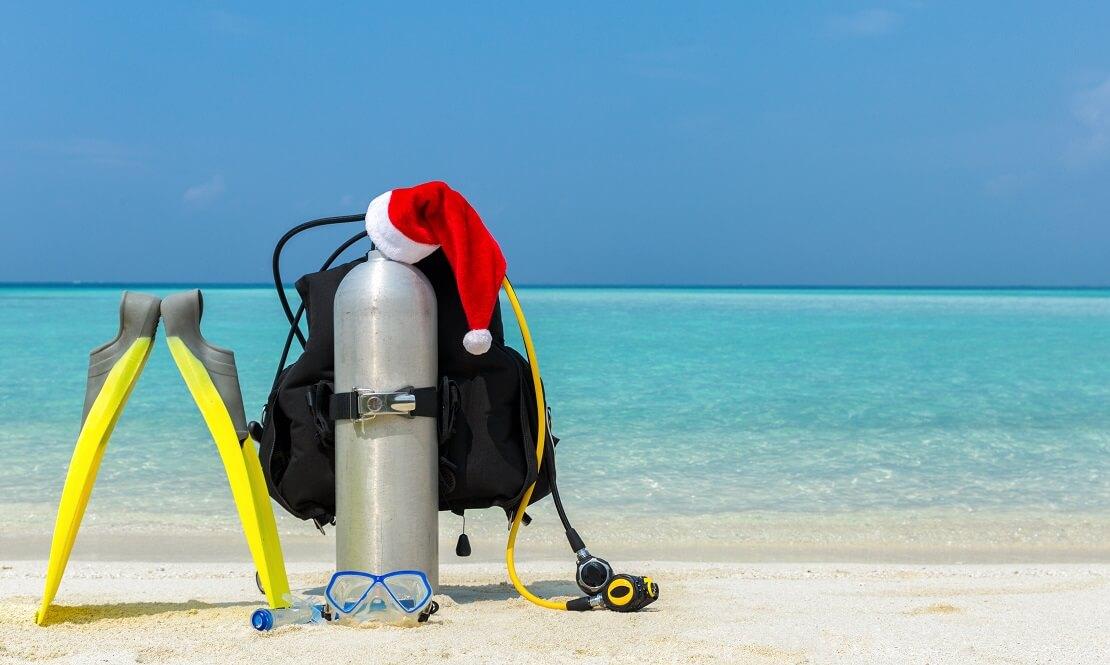 ABC Tauchausrüstung steht am Strand vor klarem Wasser auf der Pressluftflasche liegt eine Weihnachtsmütze