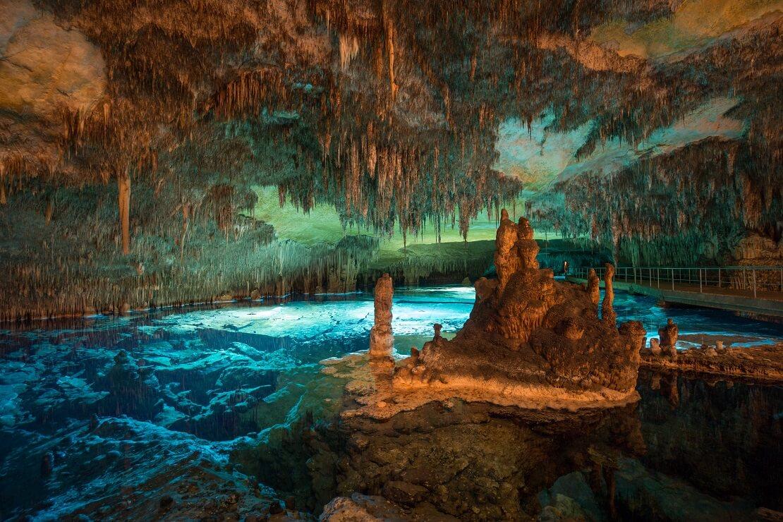 Höhle mit Stalaktiten und türkisblauem Wasser in Mallorca