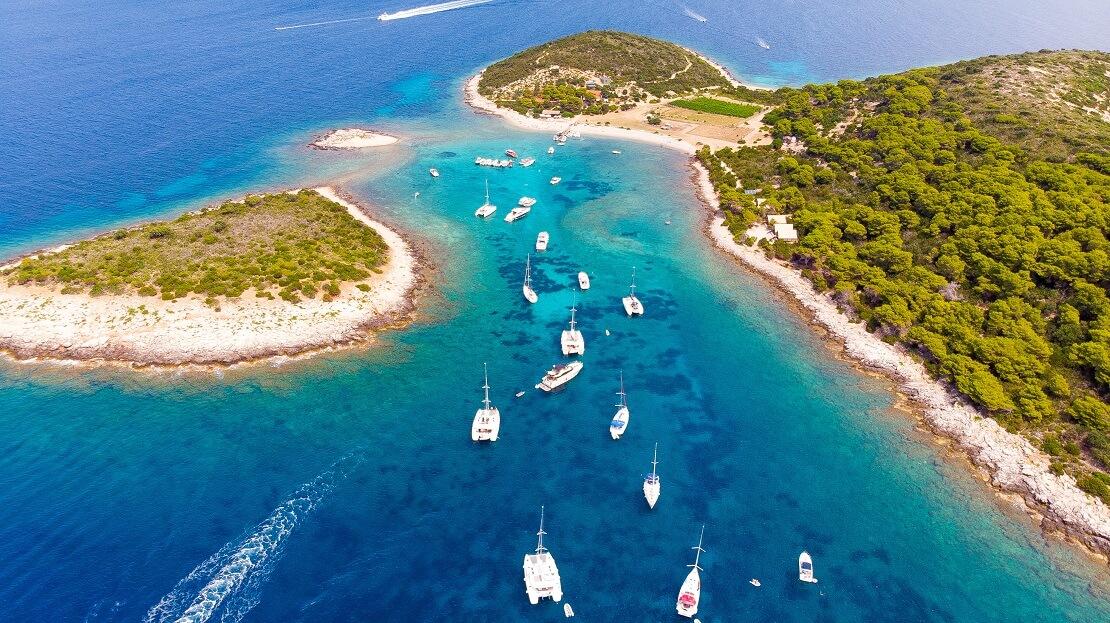 Boote schwimmen vor einer Küste im türkisblauen Meer