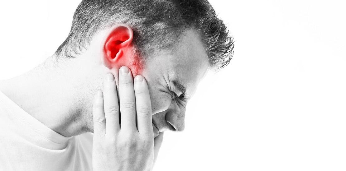 Man hält sich an sein schmerzendes Ohr