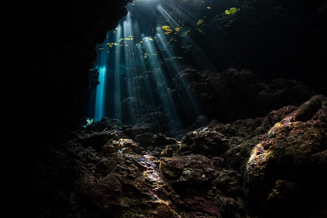 In eine Höhle unter Wasser leuchtet Licht