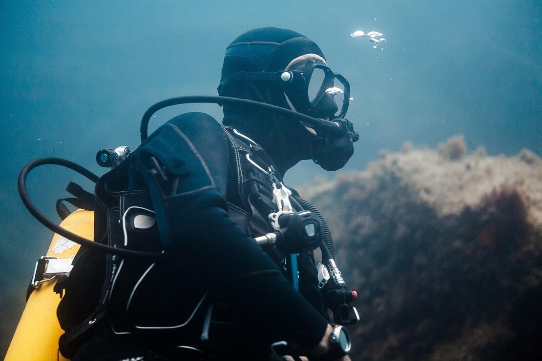 Taucher mit Atemregler im Mund unter Wasser