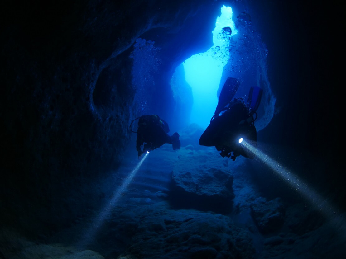 Zwei Taucher schwimmen bei Dunkelheit durch einen Tunnel mit Taschenlampen