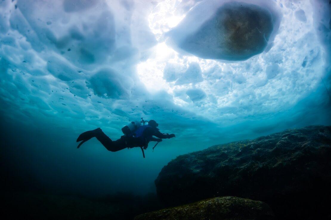 Taucher schwimmt unter einer Eisschicht