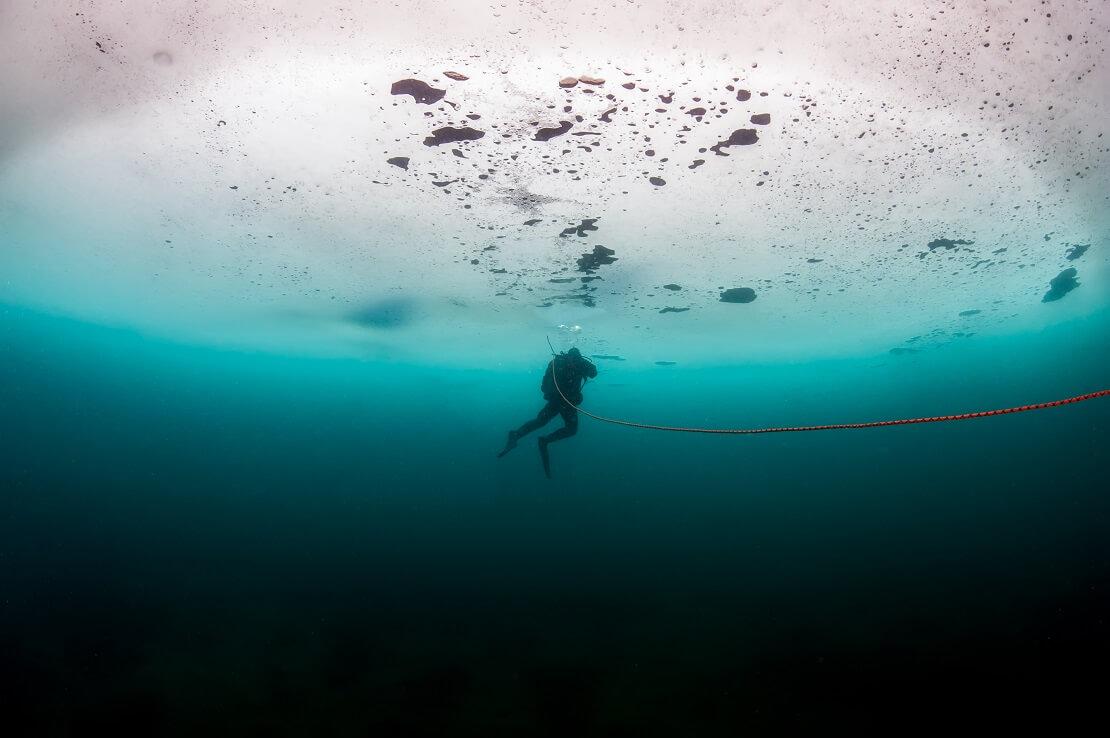 Taucher schwimmt an einem Seil entlang an einer dicken Eissicht
